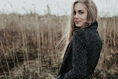 Pretty and young woman with long blonde hair dressed in wool coat looking at camera over her shoulder and smiling. Background bulr Stock Image