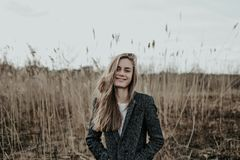 Fashion woman with long blonde hair dressed in coat looking at camera and smiling. Beautiful blonde woman with long hair in wool coat posing at camera. Girl Stock Images