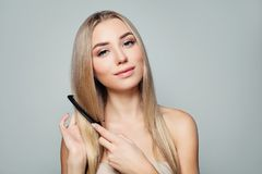 Beautiful blonde woman with long healthy straight hair combing hair. Haircare concept. Girl combs hair stock images