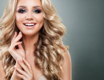 Beautiful Blonde Woman with Long Healthy Wavy Hair. And Makeup Smiling. Perfect Girl for Beauty Salon Background. Blondie Fashion Model with Permed Hairstyle royalty free stock image