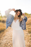 Beautiful blonde woman in a long white dress, denim jacket and hat posing in the field Stock Photos