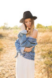 Beautiful blonde woman in a long white dress, denim jacket and hat posing in the field. Stock Images
