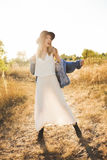 Beautiful blonde woman in a long white dress, denim jacket and hat posing in the field. Royalty Free Stock Images