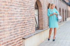 Beautiful Blonde Woman Looking At Clock Stock Image