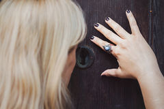 Beautiful blonde woman looking through keyhole. On an old wooden door Royalty Free Stock Photo