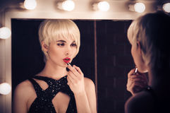 Beautiful Blonde Woman Looking Into A Mirror At Herself  Stock Photography
