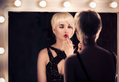 Beautiful Blonde Woman Looking Into A Mirror At Herself Royalty Free Stock Photography