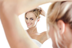 Beautiful blonde woman looking into a mirror while tying her hai Stock Photo