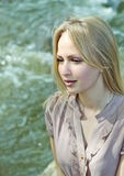 Beautiful blonde woman looking at river Stock Images