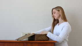 Beautiful blonde woman looking for something in jewelry boxes standing near a chest of drawers stock footage