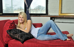 Beautiful blonde woman lounging - jeans and tank  Stock Images