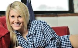 Beautiful blonde woman lounging in men's shirt Royalty Free Stock Images