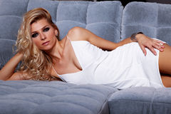 Beautiful blonde woman lying on a couch. Sensual fashion female model in white dress lying on the sofa Stock Image