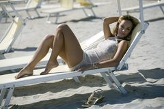 Beautiful blonde woman lying down on a deck chair Stock Images