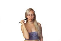 Beautiful blonde woman with makeup brush Royalty Free Stock Photos