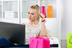 Beautiful blonde woman making shopping via internet looking in n Stock Photos