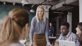 Beautiful blonde woman manager giving direction to multiethnic team. Creative business meeting at modern hipster office. stock footage