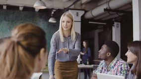 Beautiful blonde woman manager giving direction to multiethnic team. Creative business meeting at modern hipster office. Beautiful blonde women manager giving royalty free stock photos