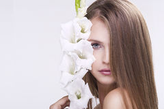 Beauty face of the young beautiful woman with flower. Female tou Royalty Free Stock Images
