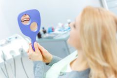 Beautiful blonde woman with mirror at dental check up Stock Photography