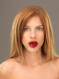 Beautiful blonde woman with mouthfull of berries Royalty Free Stock Photo