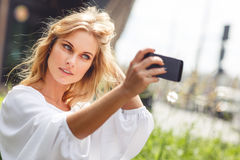 Beautiful blonde woman with natural makeup doing self portraits outdoors. Young beautiful blonde woman with natural makeup in white blouse doing self portraits stock photos