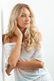 Beautiful blonde woman near white wall Stock Photo