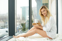 Beautiful blonde woman next to a window Royalty Free Stock Images
