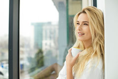 Beautiful blonde woman next to a window Royalty Free Stock Photography