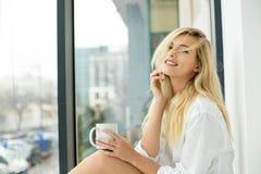 Beautiful blonde woman next to a window Stock Image