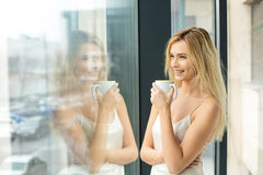 Beautiful blonde woman next to a window Stock Images
