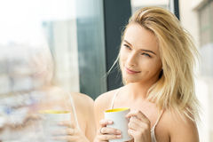 Beautiful blonde woman next to a window. Beautiful blonde woman standing next to a window, wearing night clothes and drinking coffee Stock Photos