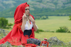 Beautiful blonde woman in old-fashioned dress and red cloak sitting on the meadow Stock Image