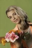 Beautiful blonde woman in orange holding flowers. Colorful portrait of a beautiful blonde girl with a retro hairstyle with curls, wearing a bright orange jacket Royalty Free Stock Photography
