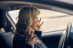 Beautiful blonde woman panic in the car. Emergency, accident, road, hazard concept Stock Photography