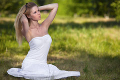 Beautiful blonde woman in park royalty free stock photography
