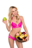 Beautiful blonde woman in pink bikini holding apple and basket with fruits Royalty Free Stock Image