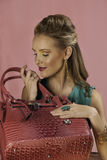 Beautiful blonde woman with pink handbag Royalty Free Stock Photo