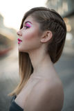 Beautiful blonde woman with pink make-up standing in the city Stock Photo