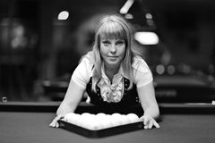Beautiful blonde woman playing  billiards Stock Image