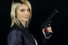 Beautiful blonde woman pointing a gun. On a black background stock photos