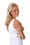 Beautiful blonde woman portrait in white dress. Beautiful blonde woman smiling in a white dress looking over her shoulder isolated background royalty free stock photography