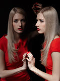 Beautiful blonde woman. Portrait of young beautiful long-haired blonde woman in red dress at mirror touching her reflection with manicured fingers stock photo