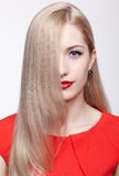 Beautiful blonde woman. Portrait of young beautiful blonde woman in red dress with half of her face behind long hair royalty free stock photography