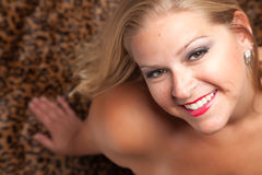 Beautiful Blonde Woman Poses on Leopard Blanket. Stock Photo