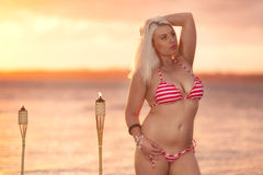 Beautiful blonde woman posing in a bikini on the beach. Royalty Free Stock Images
