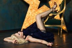 Beautiful blonde woman posing over dark background. Beautiful playful adult blonde woman wearing dark blue lace skirt and mesh stockings posing over dark Stock Photography