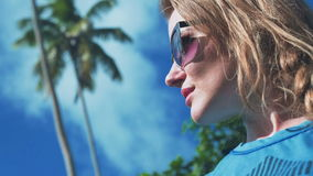 Beautiful blonde woman posing among palm trees. Young female model under palm on sea background. Vacation. Tropics. Fashion shot. Outdoors lifestyle portrait stock video footage