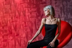 Beautiful blonde woman posing on a red background in black overalls. Valentine`s Day. Template for seasonal holiday design, poste. The Beautiful blonde woman royalty free stock image