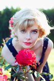Beautiful blonde woman posing in the rose garden Royalty Free Stock Photography